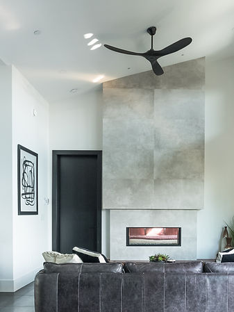 Modern living room with grey sofa, a white pillow, and double sided fireplace.