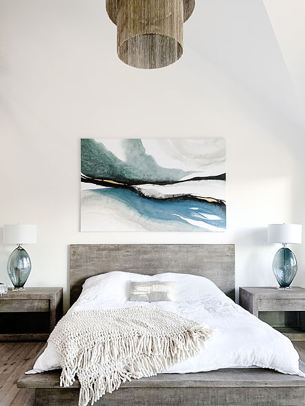 Textured bed frame with a white blanket on top and a painting hanging on the wall in Langley B.C.