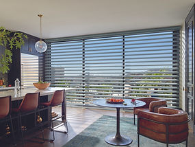 Pirouette sheers and shadings in a kitchen with brown chairs and a white countertop.