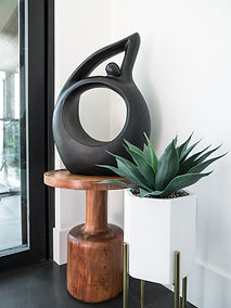 Cropped image of a black sculpture on a wooden table besides a succulent plant on a white pot.