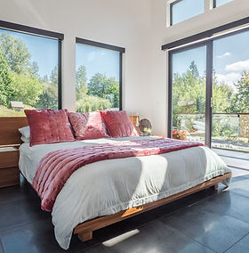 Cropped image of a modern, master bedroom with pink pillows, and large windows in Maple Ridge B.C.