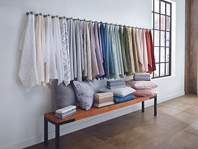 Cropped image of a design studio with a drapery and upholstery collection on the wall.
