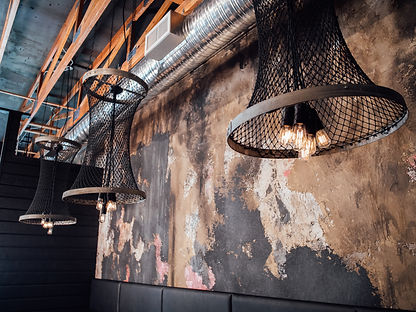 Textured wallpaper and tungsten light fixtures in the restaurant.