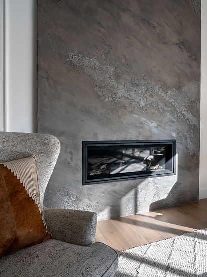 Grey textured fireplace and grey chair with a patterned pillow.