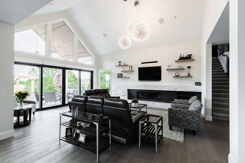 Wide shot of the living room with large sliding doors, fireplace, and white walls in Surrey B.C.