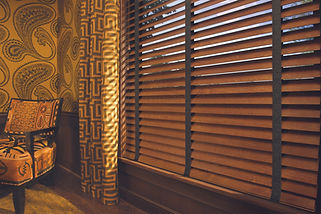 Hunter Douglas parkland, wood and metal blinds in a living room.