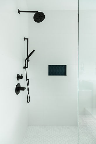 White shower room with black shower head, and glass doors.