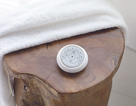 Cropped image of the Hunter Douglas white pebble remote on a wooden table.