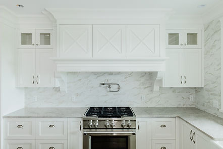 White cabinets, stove, and oven in the kitchen.