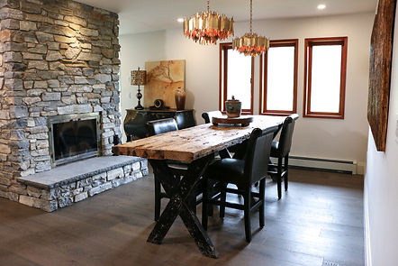 Wide angle shot of the wooden dinning room table with stone fireplace and gold light fixtures.