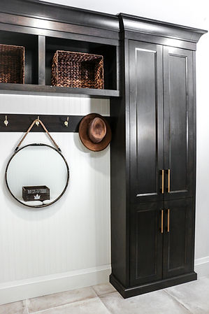 Black cabinets, hanging circular mirror, and baskets in the mudroom.