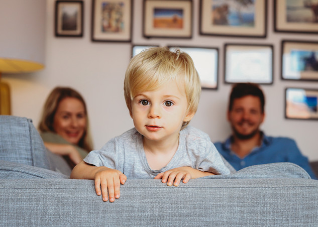 "<img src=""family photo.jpg"" alt=""Family photoshoot peekaboo boy peeking over the sofa with parents in background"">"