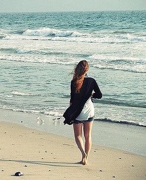 Femme marchant sur la plage, au bord de la mer : une bonne habitude anti-stress. dansmabulle-relaxation.com