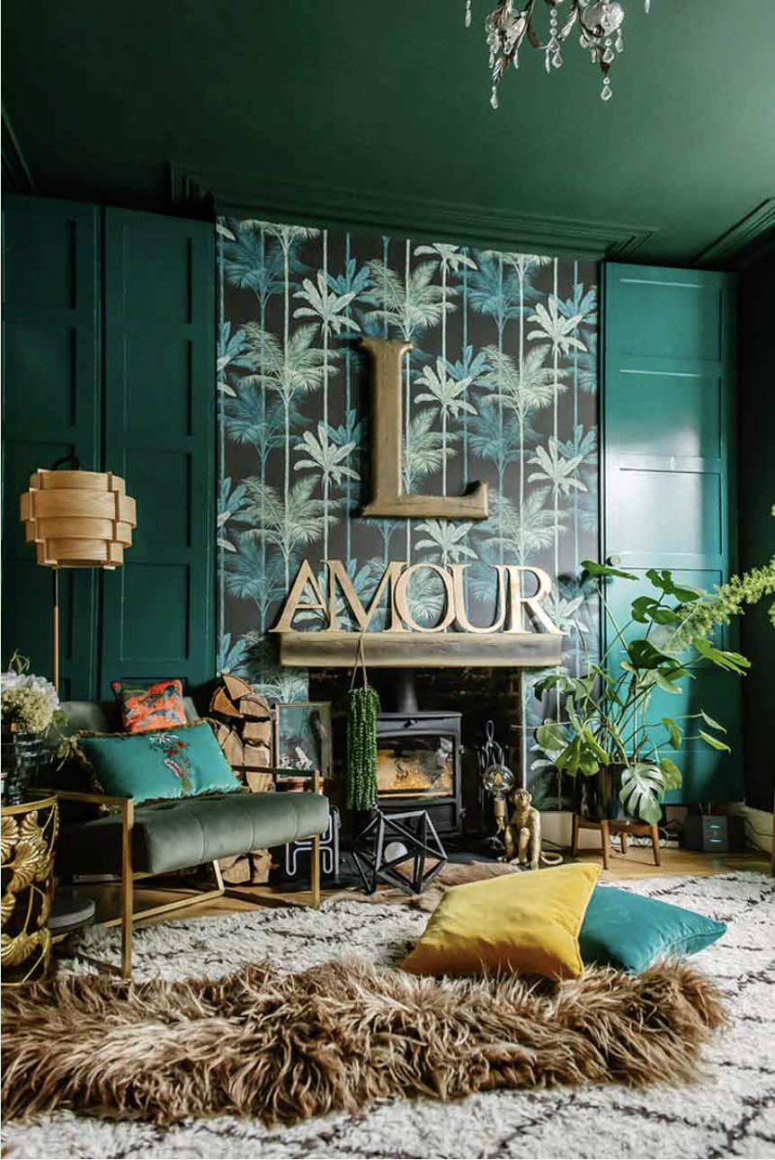 Green Living Room with Palm Wallpaper Above Wood Burning Stove and Brown Sheepskin on Floor