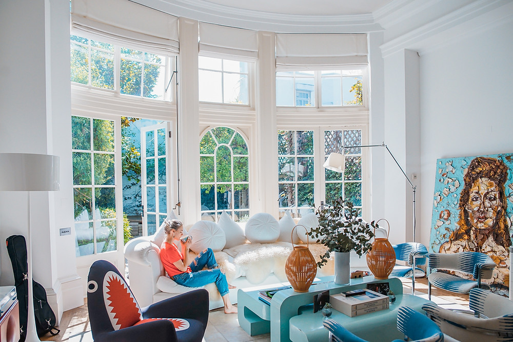White Living Room with Turquoise Coffee Table Woman sitting on White Sofa drinking Coffee