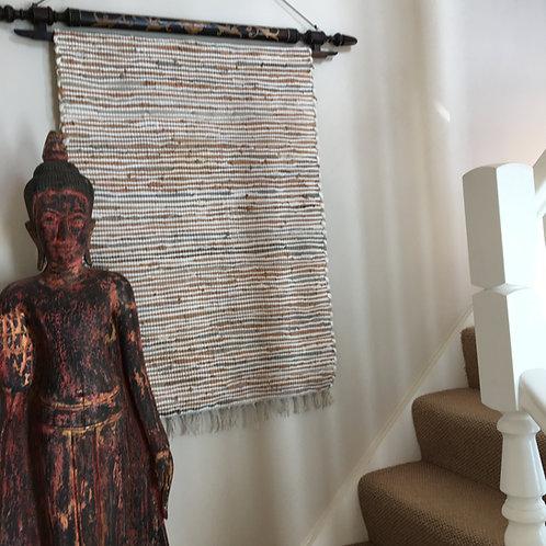 Chindi leather rag rug hanging on wall next to Buddha