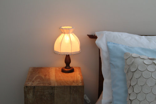 Vintage Wood Bedside Lamp next to Blue and White Pillow