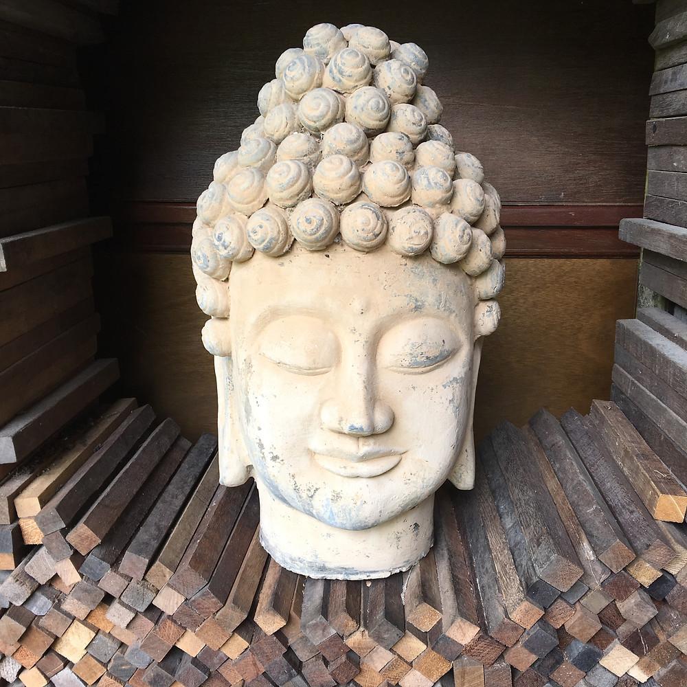 White Stone Buddha on Stack of Wood