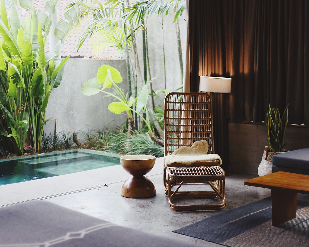 Rattan Chair with Sheepskin by Water Feature and Palm Trees