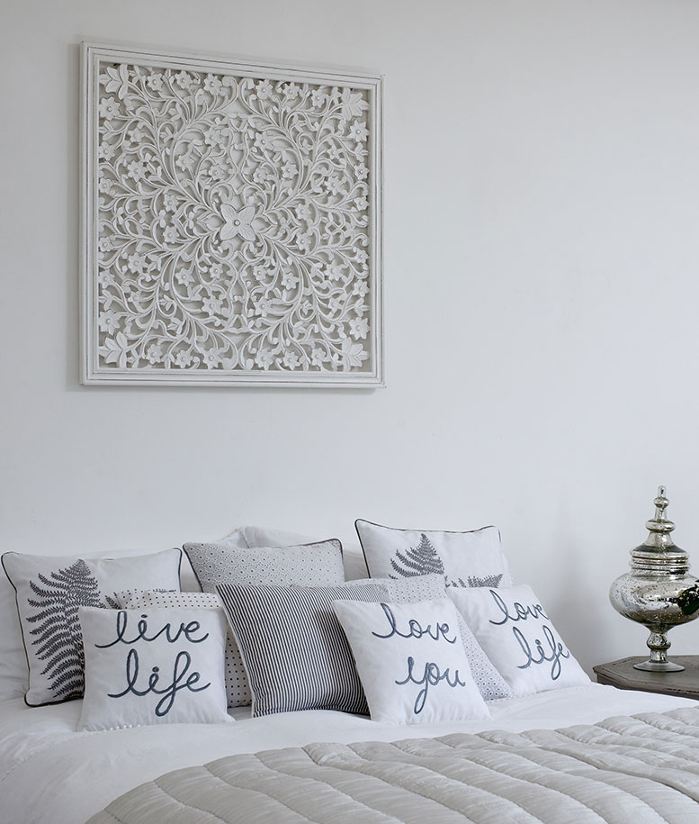 White Wood Carving on Wall above Bed with Cushions