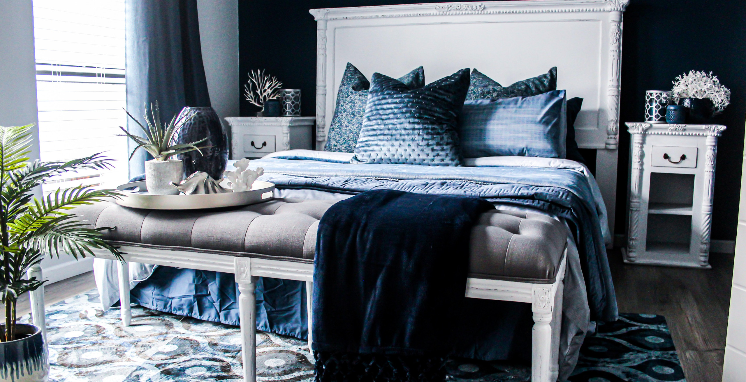 white bed with blue cushions and throw