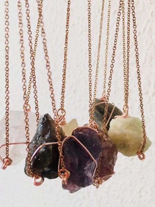 Collier court or rose avec pierre brute et non taillée en pendentif.