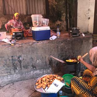 vrouwen bereiden de lokale gerechten vaak op straat