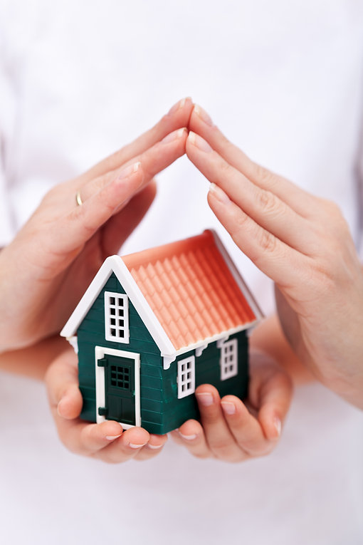 A childs hands holding a toy house with an adults hands over the roof of the house showing the house being protected.