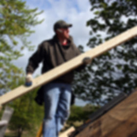 carpenter standing on roof with a board