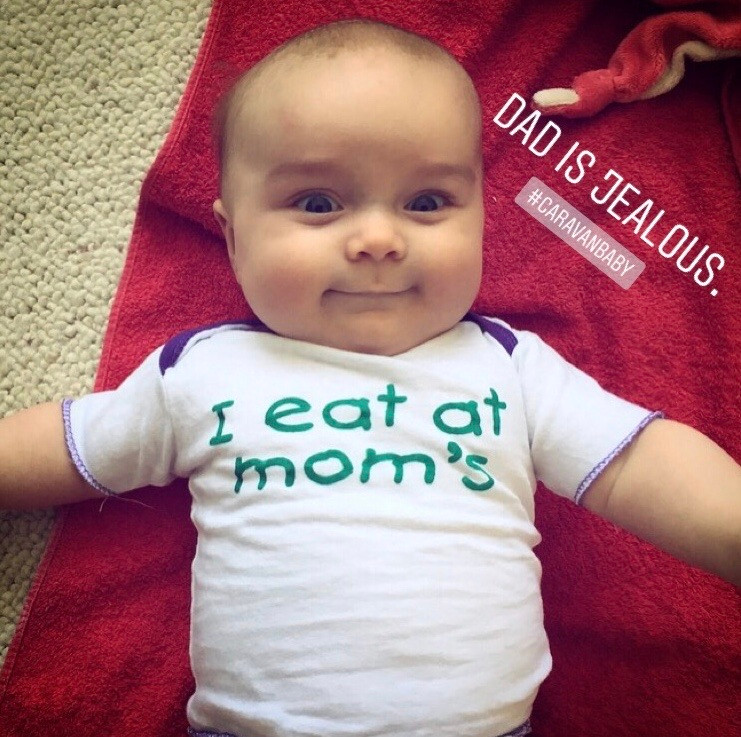 "The baby's shirt says ""I eat at mom's"" and the caption ""Dad is jealous"". The superpowers from breastfeeding are especially beneficial on travels with a caravan or van."