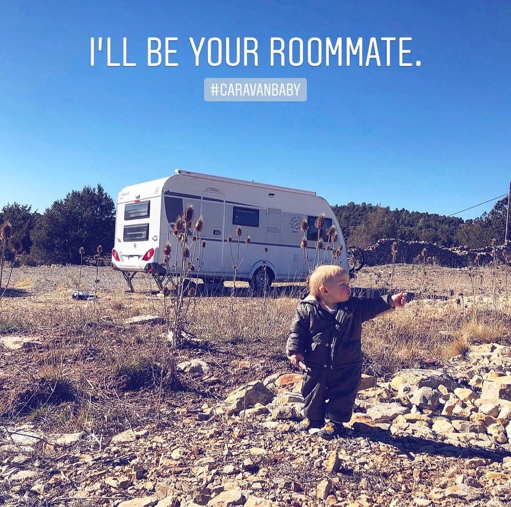 """Baby standing in front of a caravan says """"I'll be your roommate"""". Traveling Europe with a baby in a caravan instead of a motor home or a van is better in terms of room, mobility and price."""