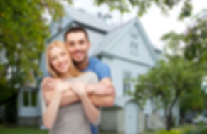 love, people, real estate, home and family concept - smiling couple hugging over house background.jp