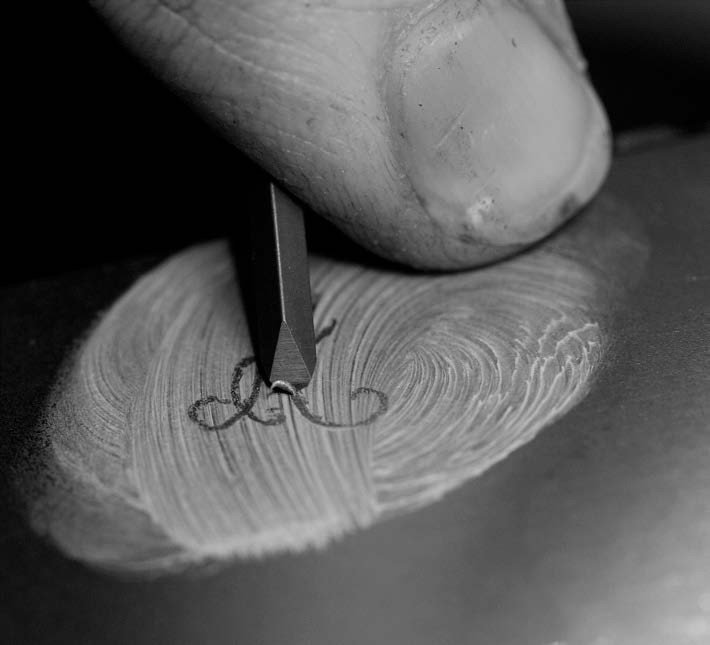"close up of engraver Ed Delorge cutting a script ""A"" into steel"