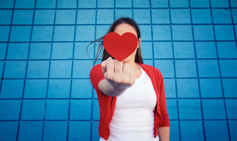A passive aggressive woman stands in front of a blue wall and flips off the camera while concealing it with a paper heart.