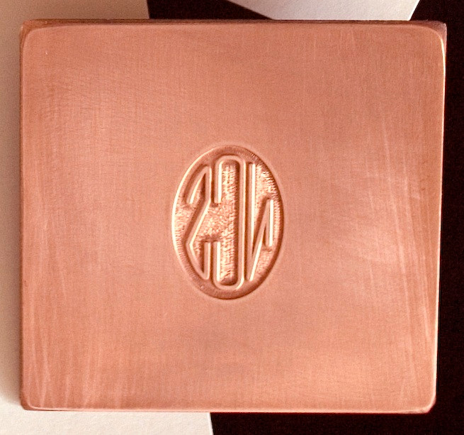Close-up of photo-engraved copper plate with author's initials designed as a monogram or cipher.