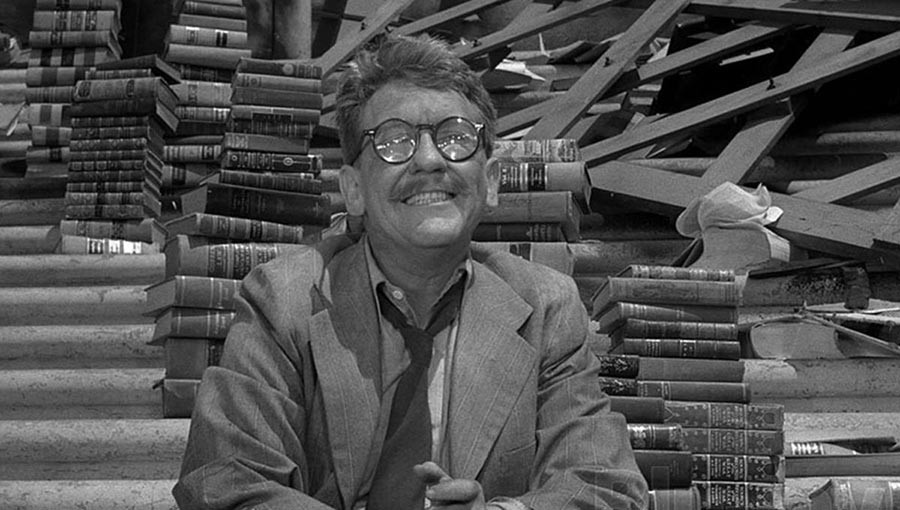 A guy smiling surrounded by books