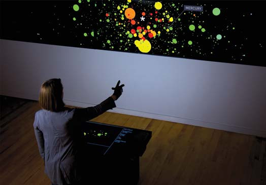 Kate Hollenbach, director of design and computation for Oblong, uses gestural commands to interact with a Kepler Exoplanet Candidates data visualization created by digital artist and designer Jer Thorp. Photo courtesy of Oblong Industries.