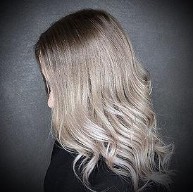 Photo d'une coupe et coiffure dame tendance ondulée couleur blond polaire