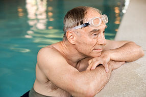 Senior man wearing goggles resting arms on pool side.