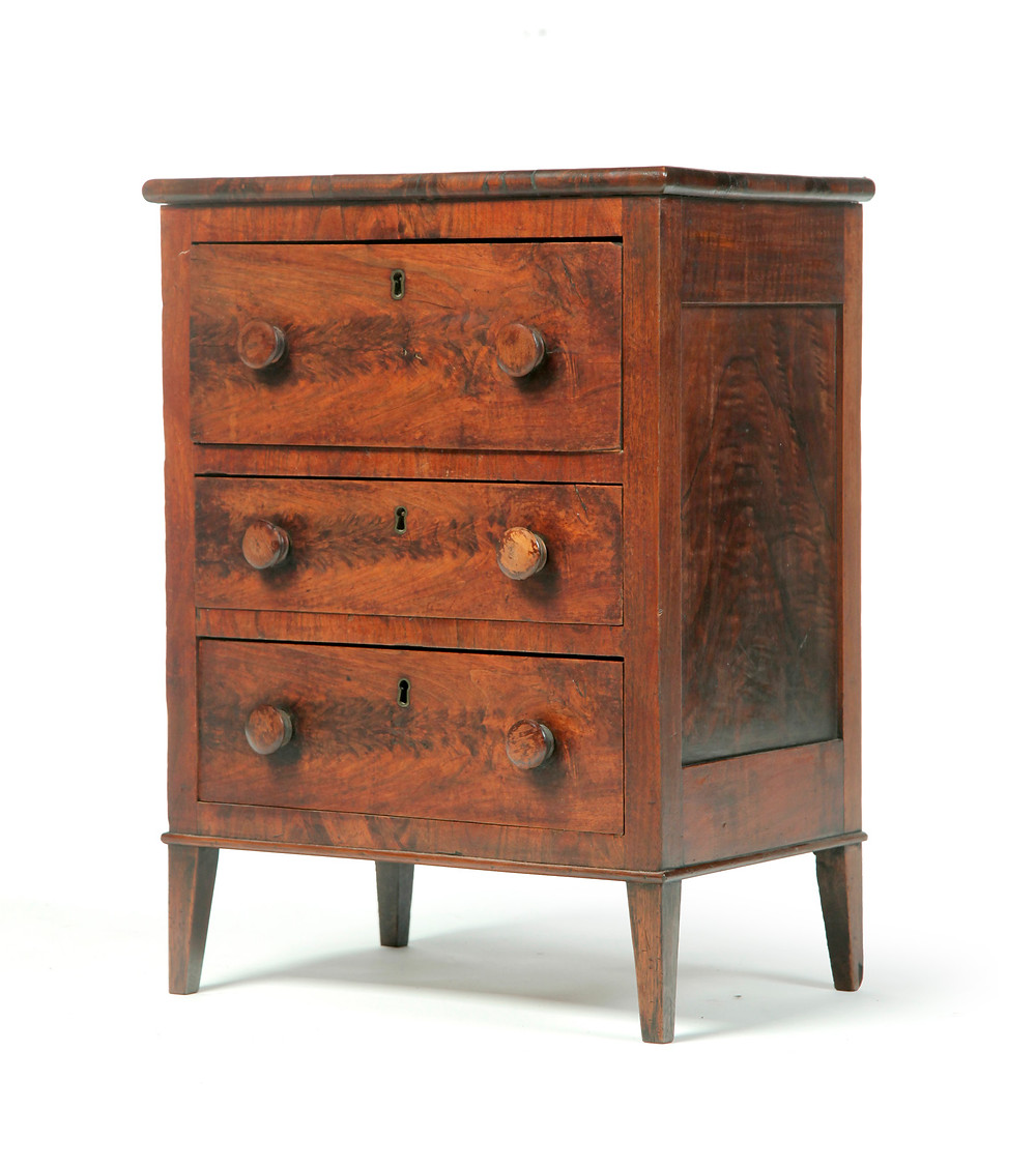 "Miniature chest of drawers, first half of the 19th century, pine and flame-grain mahogany veneer, 24"" high x 18"" wide, veneer imperfections, replaced bottom, $4080."