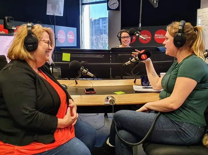 Three woman talk into microphones in a Radio studio
