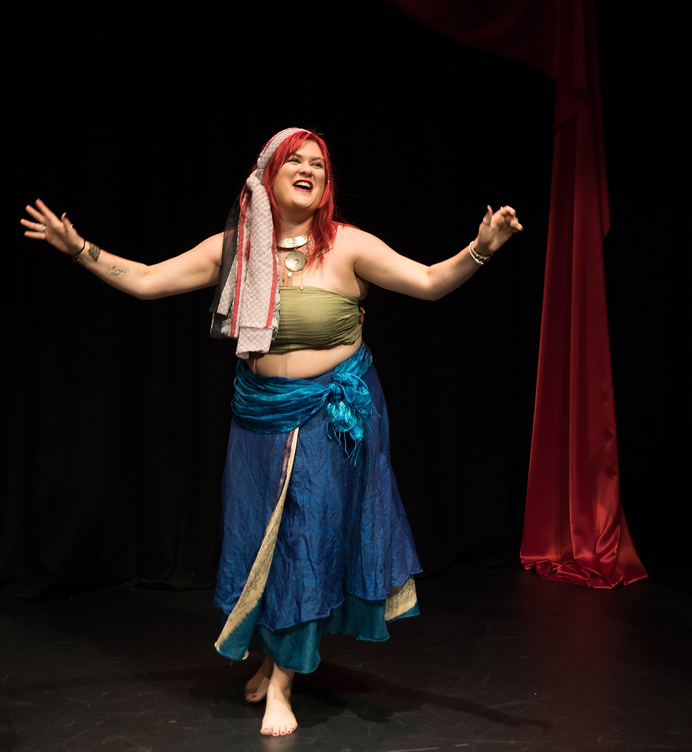 A woman on stage in gypsy clothes