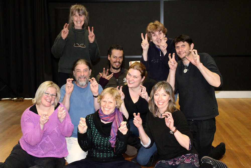 A group of actors posing for the Camera making bunny ears with their fingers