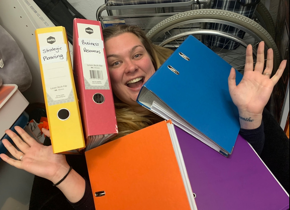 A woman smiles with folders piled on top of her