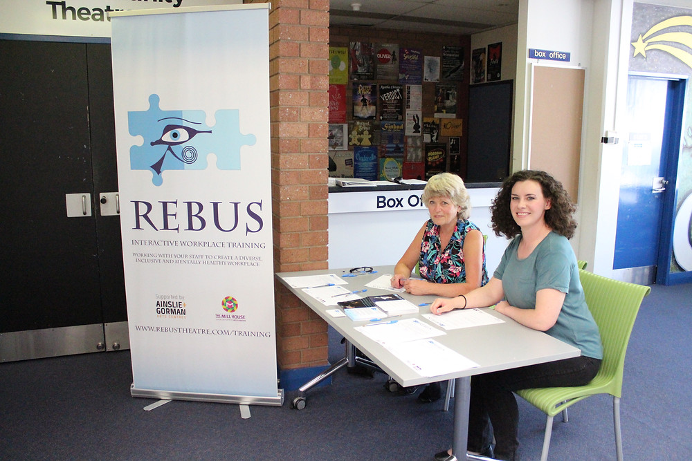 Two women sit at a table smiling at the camera next to a Rebus banner