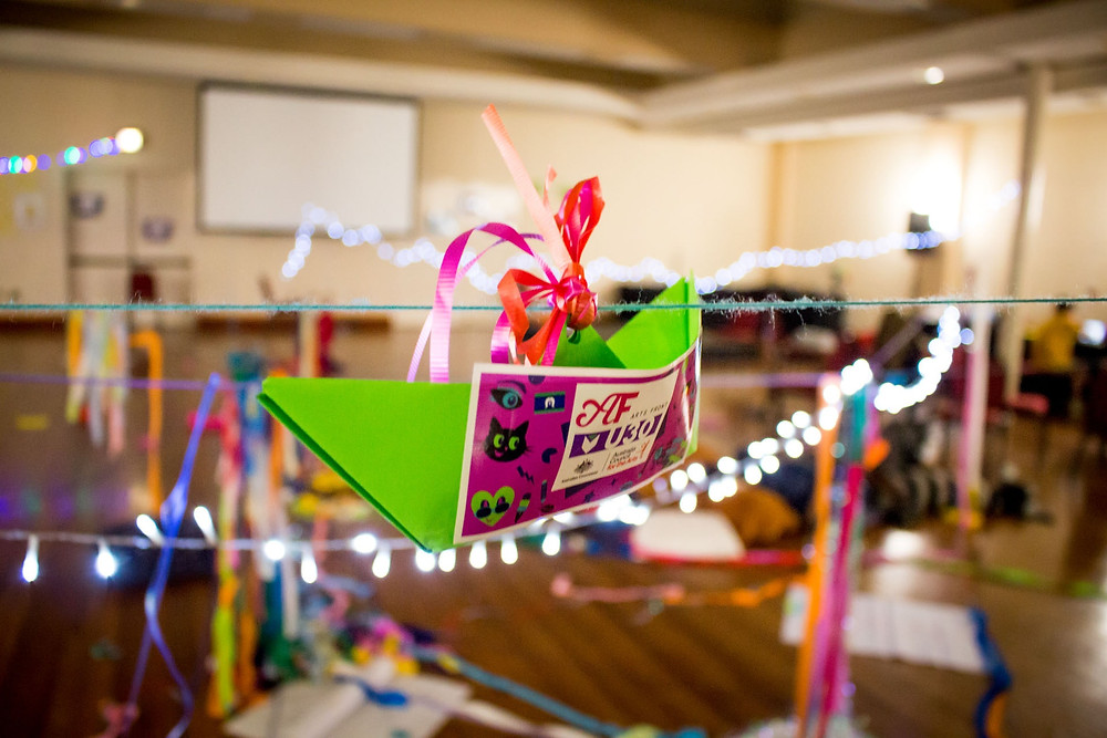 Image of Arts Front Flyer hanging from an Origami Boat on a piece of string