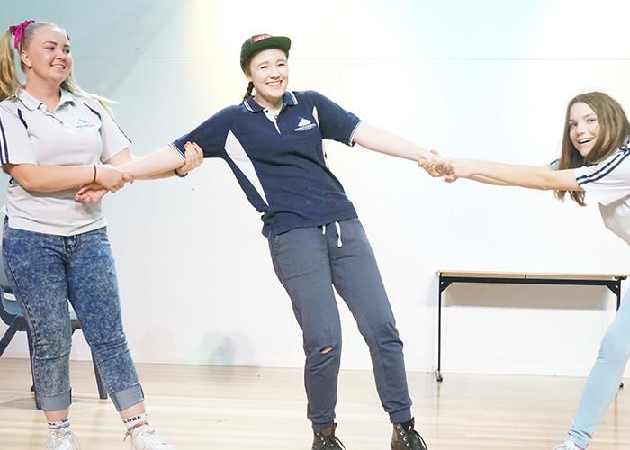 Three women hold hands