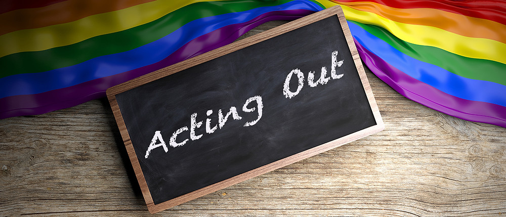 A Blackboard with 'Acting Out' written on it, a rainbow flag is arranged around the blackboard