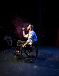 A man balancing on the back wheels of a wheelchair, Daniel Savage, popping a balloon filled with glitter.