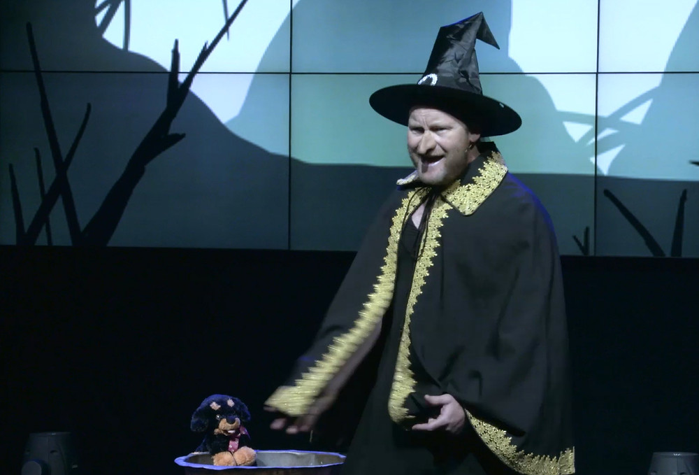 A man standing on a stage in a witches costume
